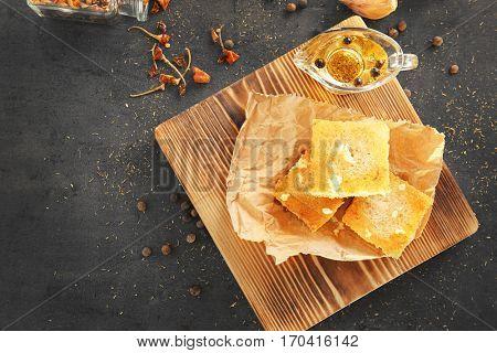 Tasty garlic French bread slices on wooden board