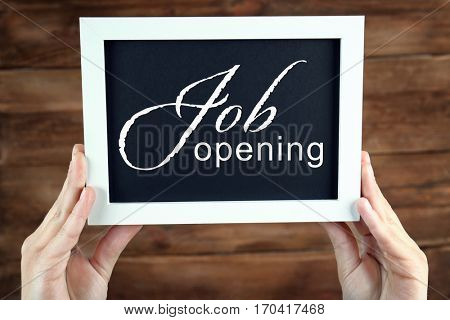 Labor market concept. Female hands holding chalkboard with text JOB OPENING on wooden background