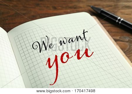 Labor market concept. Text WE WANT YOU in notebook on wooden table