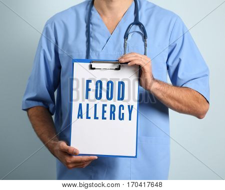 Health care concept. Doctor holding clipboard with text FOOD ALLERGY on color background