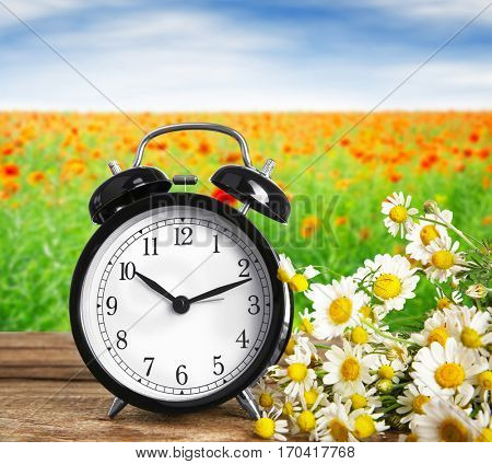 Alarm clock with flowers on wooden table against landscape background. Time change concept