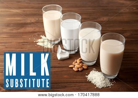 Food substitute concept. Glasses with different milk on wooden background
