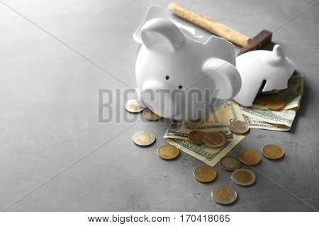 Broken piggy bank with money and hammer on table