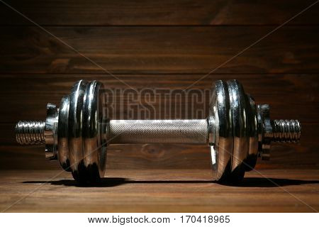 Metal collapsible dumbbell on wooden background, closeup