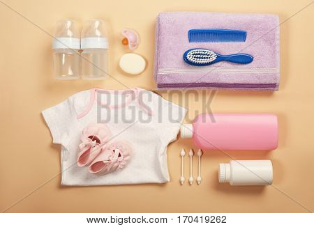 Baby clothes and necessities on color background