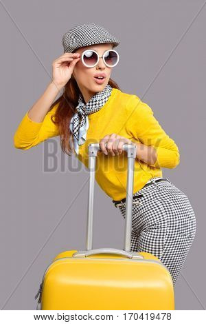 Fashionable woman with yellow suitcase, travel concept