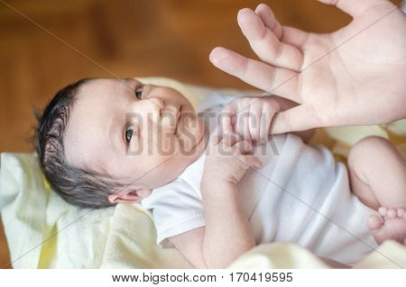 two weeks old newborn baby in the hands of father. baby holds hands thumbs. Child with hormonal birth rash