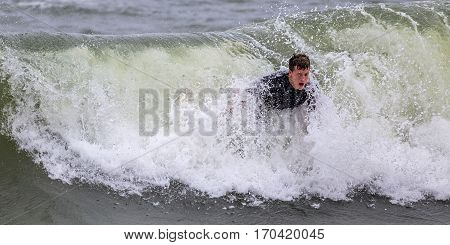 A young man in late teenage years surfing in the ocean. He is lying on a surfboard that is submerged in a wave. With the surfboard submerged it looks as if he is bodysurfing.