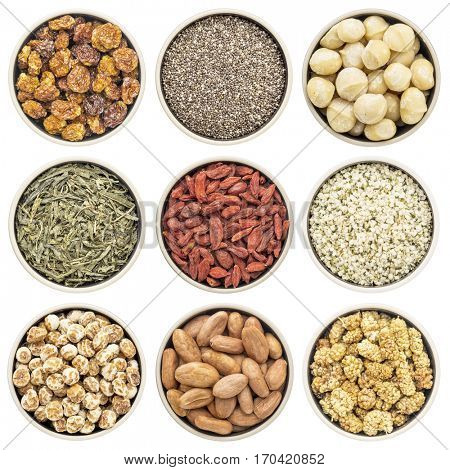 superfood collection (goldenberry, chia seeds, macadamia nuts, green tea, goji berry, hemp seed hearts, tigernuts, cacao beans, mulberry) - top view of isolated round glass bowls