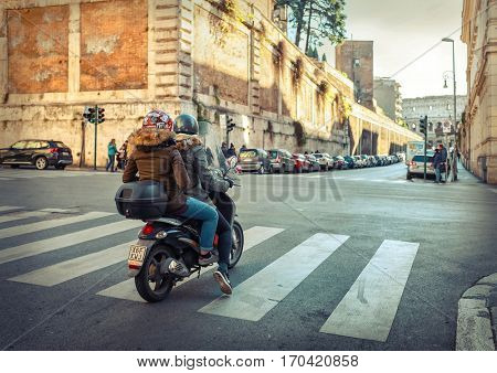 ROME - JANUARY 07: People on scooter near the Coliseum January 07, 2017 in Rome. Roman Coliseum and scooters are the symbols of Rome - most popular historical travel place of the Italy and the world.