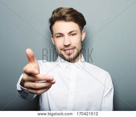 Business man with hand extended to handshake  over grey background