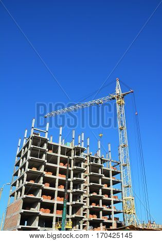 Construction industry with Crane Copy Space Sky Background. Crane Building New House on the Construction Site. Building cranes and building under construction.