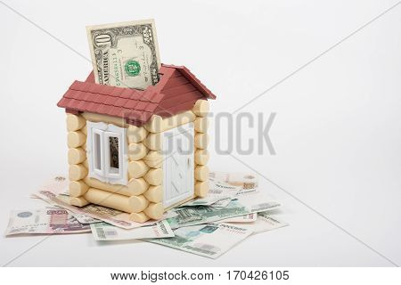House Stands On The Banknotes Of Russian Rubles, From The Roof Sticking Out Of Ten Us Dollars Bankno