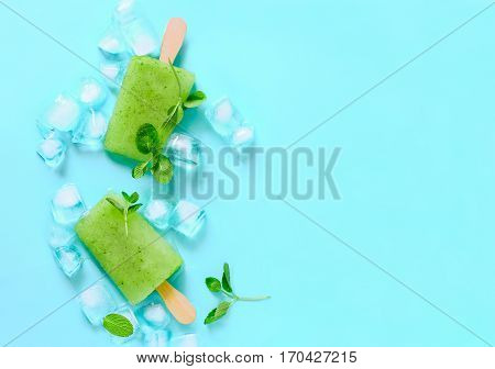 Green refreshing mint popsicles with ice cubes decorated with mint leaves view from above