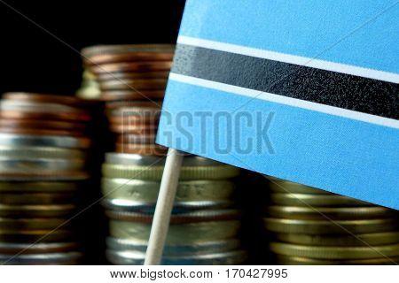 Botswana Flag Waving With Stack Of Money Coins Macro