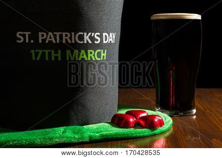 Closeup of St Patrick day with a pint of black beer and hat over a table and black background
