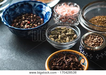 Various spices in a ceramic bowl on slate partial blur horizontal