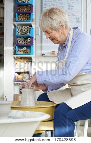 Senior Woman Working At Pottery Wheel In Studio