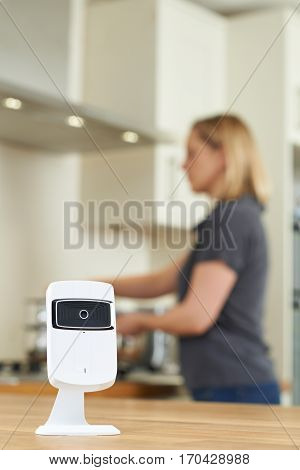 Smart Security Camera In Kitchen As Woman Prepares Meal