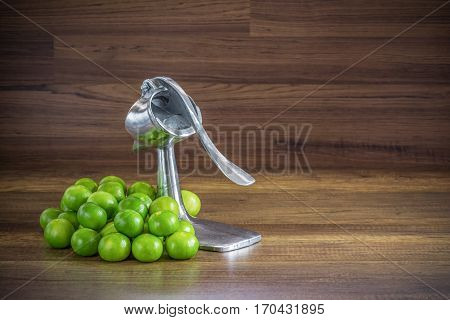 stack of green lemon with aluminum manual juicer squeezer fruit press on wood