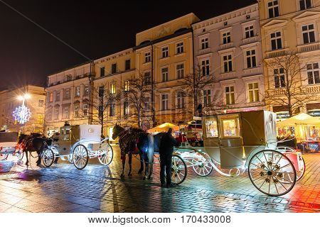 Krakow, Poland - January 22, 2017: Horse-drawn Carriage Before The Sukiennice On The Main Market Squ