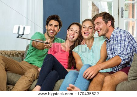 Group of friends sitting on sofa and a taking a selfie at home