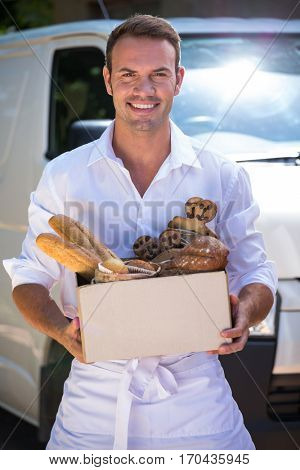 Portrait of delivery man holding parcel standing in front of his van