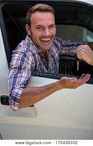 Portrait of young man receiving car keys in his car