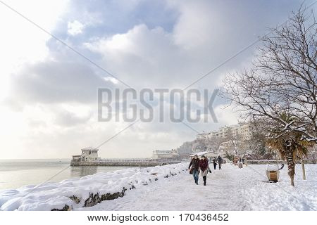 ISTANBUL, TURKEY, FEBRUARY 8, 2017: People walking on the snow covered coastal park at Kadikoy Moda, famous outdoor landmark in Istanbul, Turkey.