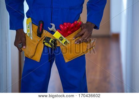 Mid section of handy man wearing tool belt at home