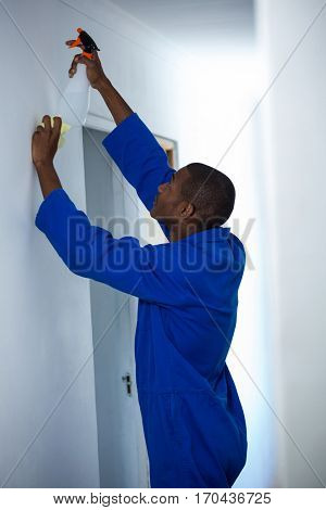 Handyman spraying insecticide on wall at home