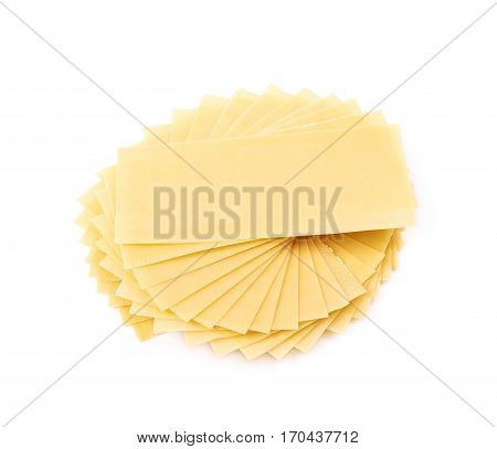 Twisted pile of dried lasagna pasta sheets isolated over the white background