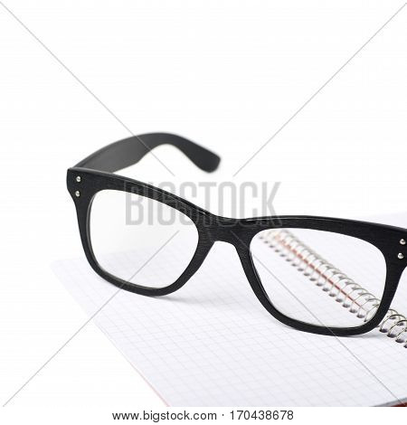 Reading glasses over a squared paper notebook isolated over the white background, close-up crop composition