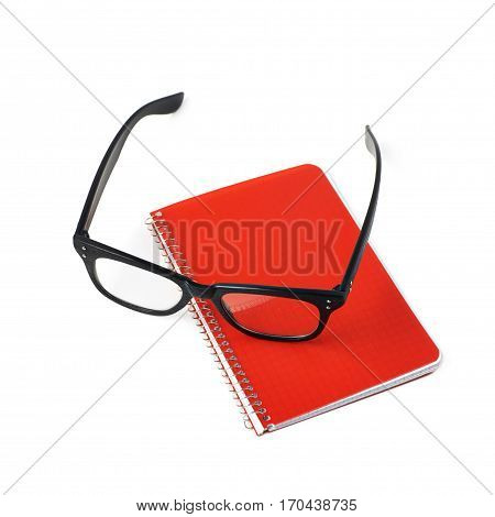 Reading glasses over a squared paper notebook isolated over the white background