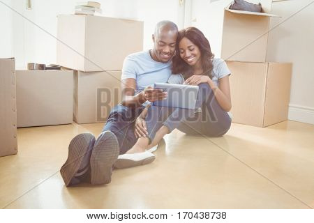 Young couple using digital tablet in their new house