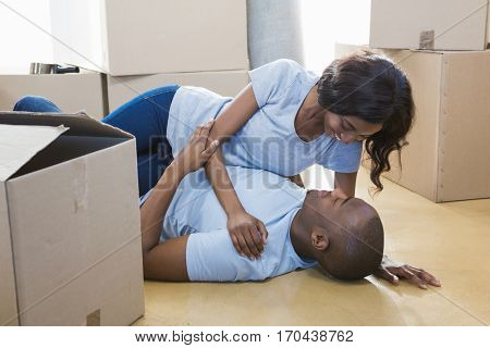 Young couple cuddling on the floor while unpacking box in their new house