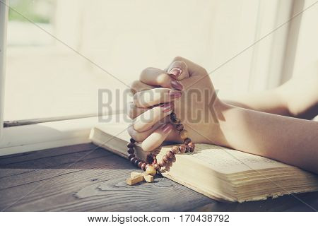 woman hand cross on the book in wooden