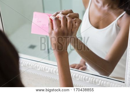 Reflection of woman sticking I love you word sticky note on mirror