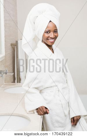 Portrait of young woman wearing white bathrobe standing in the bathroom
