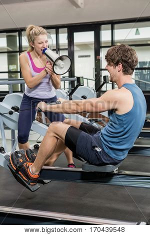 Trainer yelling through a megaphone while man on rowing machine at gym
