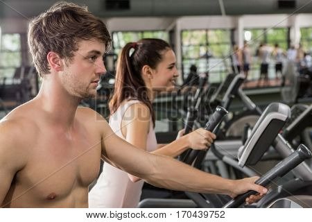 Man and woman exercising on the elliptical machine at gym