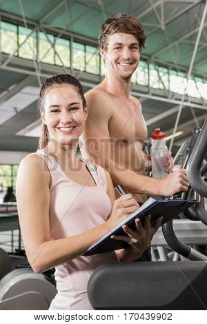 Trainer writing on a clipboard while man exercising on a elliptical machine at gym
