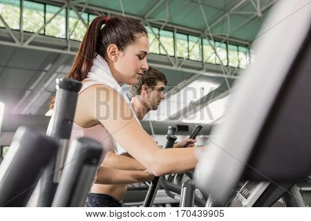 Woman and man exercising on the elliptical machine at gym