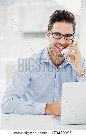 Portrait of businessman talking on phone in office