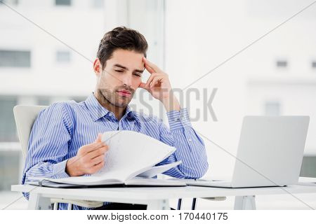 Worried businessman looking at diary in office