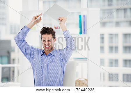 Frustrated businessman throwing laptop in office