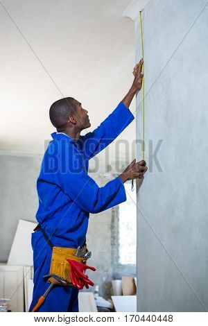 Handyman measuring a wall in a new house