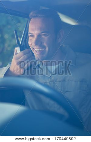 Delivery driver talking on walkie-talkie while sitting in his van