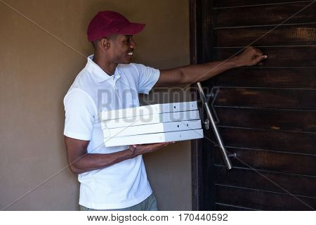 Pizza delivery man with pizzas boxes knocking a door