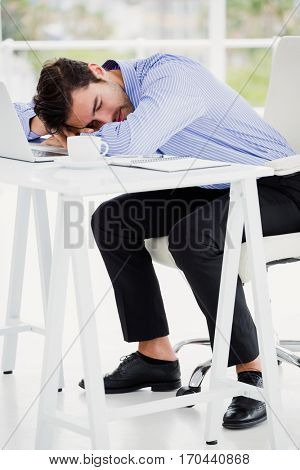 Businessman putting his head down on desk in office